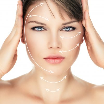 Laser therapy on pretty woman face over white background. Young attractive Caucasian female ready for cosmetic operation.